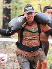 Paul Lachance, one of thousands of runners set to participate in the Asheville Super and Sprint at Grove Stone & Sand on Aug. 4 and 5, carries a sandbag in a Spartan Race last year.e