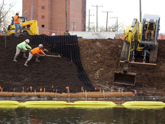 """Work crews spread soil over a """"geocell"""" as part of phase one of DuPont's South River mercury remediation plan."""