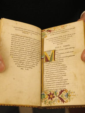 Curator Steve Glabraith holds a rare copy of Horace, printed in the 1500s, at the Cary Collection and Library located inside the Wallace Center on the campus of RIT in Henrietta.
