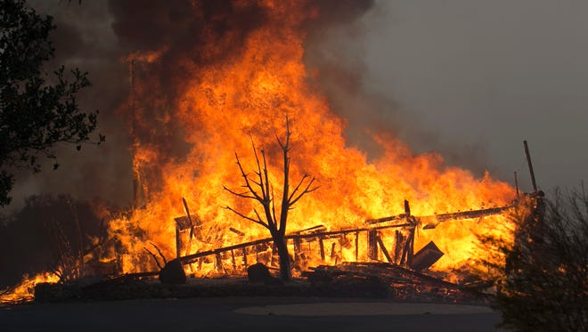 Flames from a wildfire consume a home  east of Napa, Calif., on Oct. 9, 2017.