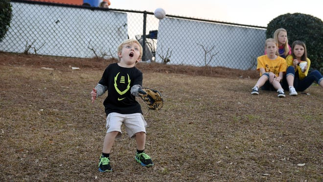 Dylan Wilson, 4, plays catch with his dad during Southern Miss baseball's season opener Friday at Pete Taylor Park.