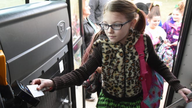 Winslow School second-grader Karlee Gannotta scans her Z Pass card while boarding a bus.