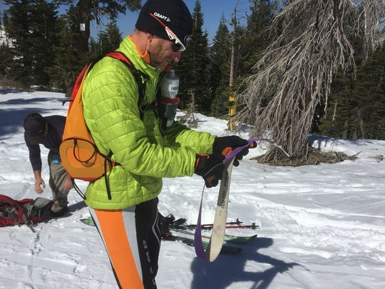 Transition time: Dave Riggs, 53, of Truckee, Calif., folds up the skins he had on his skis to gain traction for climbing uphill at Sugar Bowl Resort on March 6, 2015. With skins removed he can ski downhill with the rest of the crowd.
