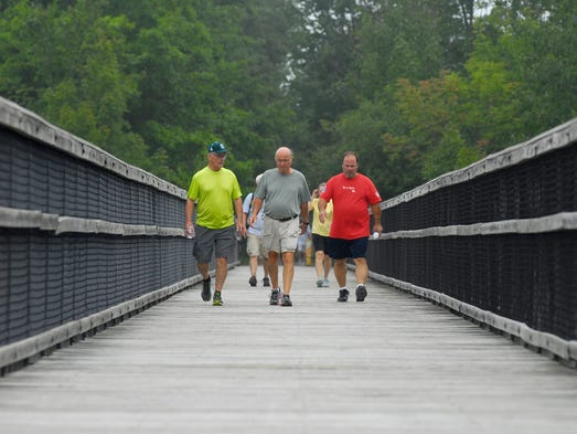 (From left) Dick Engelgau, of Port Huron, Larry Howard, of Grant Township, and Bill Strauch, of Clyde Township, walk over the Mill Creek Trestle, Mon, Sept 1, during the annual Trek the Trestle Trail Walk in Avoca.