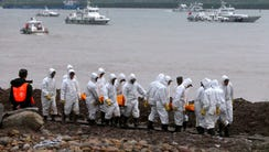 Rescuers carry victims' bodies along the Yangtze River