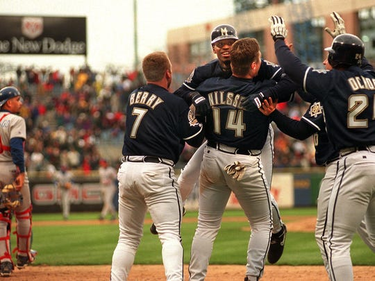 Lou Collier leaps into the arms of teammates Sean Berry, Dave Nilsson and Alex Ochoa after scoring the winning run in the bottom of the ninth inning. Cubs catcher Benito Santiago (far left) can only watch the Brewers' celebration. The Brewers scored 5 times to beat the Cubs 5-4 Saturday, April 17, 1999.