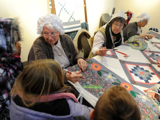 Jane Eberhart, left, explains quilting techniques to students who were visiting a previous Spring Farm Fest at Angel Mounds. The event showcases different aspects of Indiana farming culture through the ages.