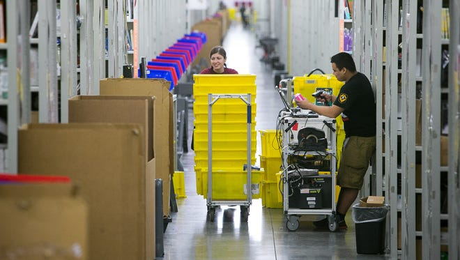 Amazon Prime is offering same-day delivery to much of the Phoenix area starting May 27. In this March 2015 file photo, employee Amanda Bailey pushes a cart for items at the West Mohave Street fulfillment center.