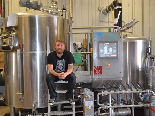 Artist Matt Ritter sits in his brew house at Catawba Island Brewing Company, where Ritter is the head brewer. The job allows him to apply his creative side just has he does through painting in his spare time.