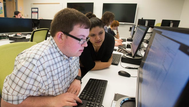 University of West Florida students Ian Briggs, left, and Jessica Aguilar work on a computer program in the Battle Lab at UWF on Wednesday, April 5, 2017.