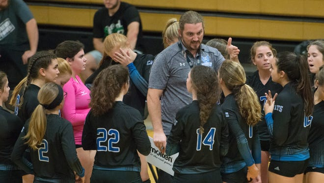 Coach Steele talks with the team in between games during the first round match between Booker T. Washington and Pine Forest high schools in the Volleyball District Tournament at Milton High School on Monday, October 16, 2017.