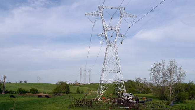 New Dominion Virginia Power transmission line towers in Stuarts Draft off White Hill Road. The old rusted tower lies beneath the new galvanized tower.   In the background stands a new three tower design that is designed to handle added stresses directional changes. In the distance is an old tower that has not been replaced.