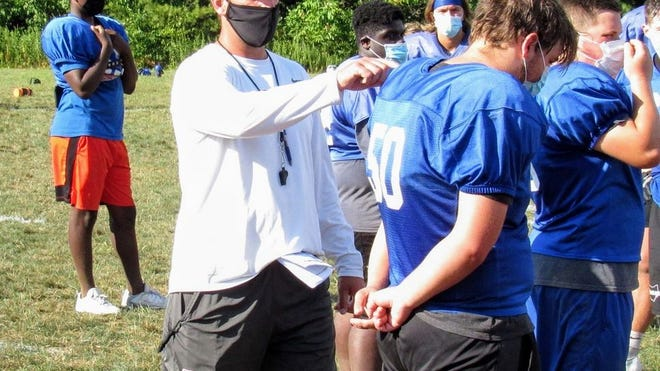 "Olentangy Orange football coach Zebb Schroeder conducts practice Aug. 17 while wearing a face covering. Gov. Mike DeWine announced Aug. 18 that all fall sports can ""move forward."""