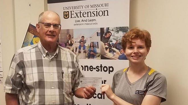 Rachel Buenemann, County Engagement Specialist for the University of Missouri Extension in Phelps County received a check from John Sullivan of the Rotary Breakfast Club of Rolla.
