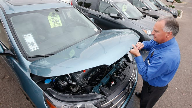 Mike Johnson, a sales manager at a Honda  dealership in Tempe, Ariz., opens the hood of a Honda CR-V SUV Dec. 2, 2014. Researcher Experian Automotive says average new-car loan in the fourth quarter hit a record $28,381 and the average monthly payment was a record $482. .