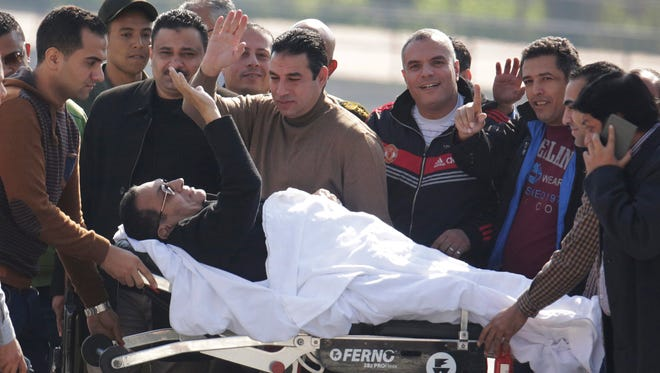 Former Egyptian President Hosni Mubarak, 86, greets medics, army personnel and his supporters, as he leaves a helicopter ambulance after it landed at Maadi Military Hospital following his verdict in Cairo, Egypt, Saturday, Nov. 29, 2014. An Egyptian court on Saturday dismissed criminal charges against former president Hosni Mubarak in connection with the killing of protesters in the 2011 uprising that ended his nearly three-decade reign.