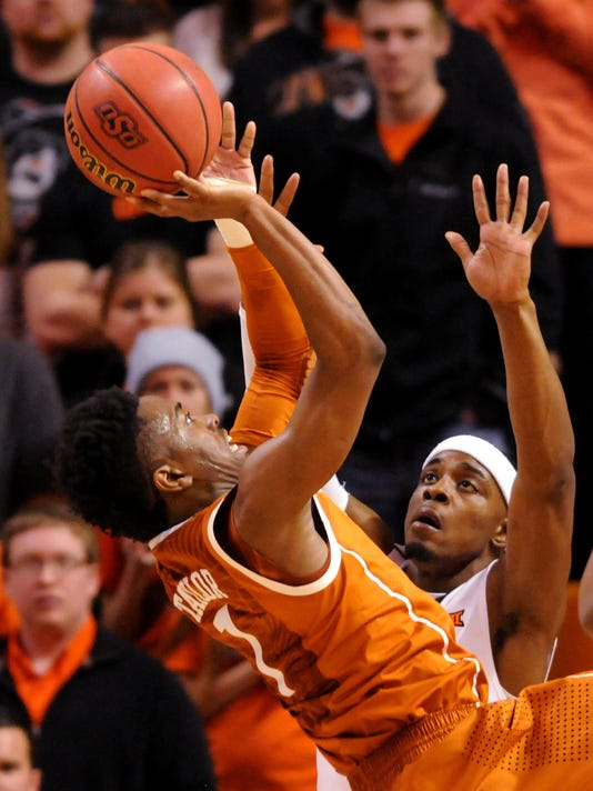 Texas guard Isaiah Taylor, left, takes a shot over Oklahoma State guard Anthony Hickey, Jr. during the first half of an NCAA college basketball game in Stillwater, Okla., Saturday, Jan. 10, 2015. (AP Photo/Brody Schmidt)