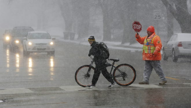 A crossing guard at Bowen Street and Melvin Avenue stops traffic Wednesday for a bicyclist.