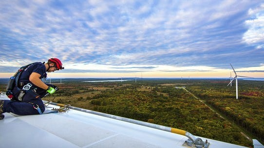 Worker on top of wind turbine with other turbines in the distance.