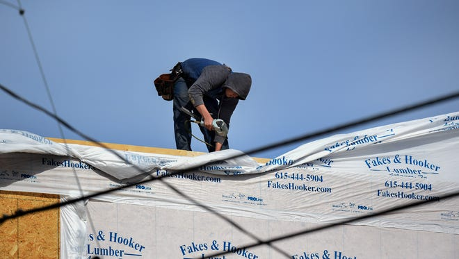 Construction workers work on the roof of a new home without protection on Fern Ave in Nashville Tenn., Thursday, April 5, 2018.
