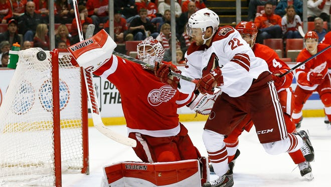 Detroit Red Wings goalie Jimmy Howard (35) deflects a shot by Arizona Coyotes left wing Craig Cunningham (22) during the third period of an NHL hockey game in Detroit on Tuesday, March 24, 2015. Arizona won 5-4 in a shoot-out.