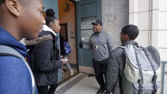 Teaching assistant Leonardo Baker, second right, greets students arriving at Franklin High School Wednesday morning, Dec. 12, 2018, in Seattle. High school students are getting more sleep in Seattle, according to a study on later school start times. Teenagers at Franklin and another Seattle high school wore activity monitors to discover whether a later start to the school day would help them get more sleep. It did, adding 34 minutes of slumber a night, and they reported less daytime sleepiness and grades improved. The Seattle School District changed from a 7:50 a.m. start time to 8:45 a.m. in the fall of 2016 for high schools and most middle schools, joining dozens of other U.S. school districts adopting later starts to fight teen sleep deprivation. (AP Photo/Elaine Thompson)