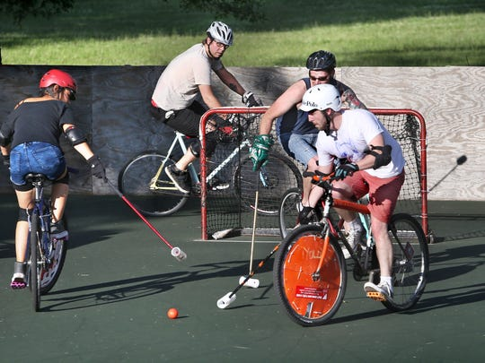 Indy Bike Polo members practice on a court set up with goals in Arsenal Park at 46th and Haverford on Tuesday, July 1, 2014. Shown left to right are Amy Chi, Tucker Schwinn, Ross Robertson and Jeff Kelly.