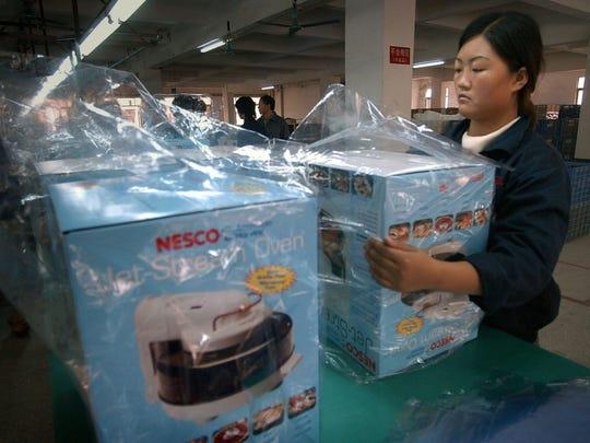 Zhu Ai Tang, 19, wraps finished Nesco products at Panint