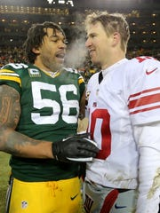 Green Bay Packers outside linebacker Julius Peppers (56) and New York Giants quarterback Eli Manning (10) speak following their NFC wild-card game at Lambeau Field.