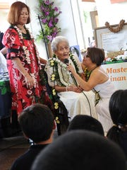 """In this file photo, master healer Josefa """"Tan Pai"""" Certeza, seated, is accompanied by her daughter, Abbie Certeza Guerrero, standing left, and granddaughter, Veralynn Guerrero Sanchez, as she speaks during a poster-unveiling ceremony held by the Guam Council on the Arts and Humanities at the Chamorro Village."""