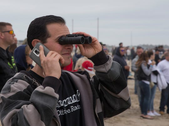 William Napoli of Brick talks on the phone as he watches the races with his binoculars during the 2016 Offshore Grand Prix in Point Pleasant Beach on May 22, 2016