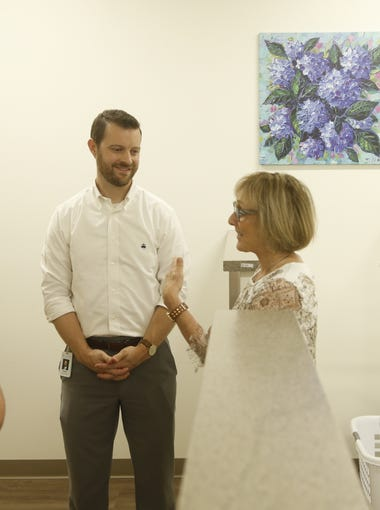 Circle the City Sister Adele O'Sullivan (left), Circle the City CEO Brandon Clark (center) and Annette Stein talk Aug. 9, 2018, inside the women's area at Circle the City's new facility in Phoenix.
