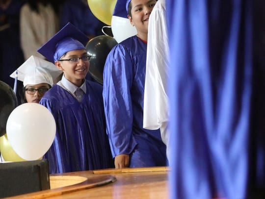 Students wait to step on stage to receive their diplomas
