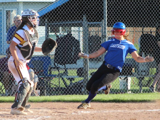 Sophomore Madison Wasen (right) races across the plate to score the Blazers' third run Friday in the final softball game played at Ladywood.