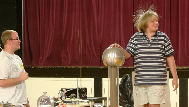 As part of a science assembly electrical demonstration last Friday, YIS student Nicholas Bickford's hair stands up as he touches a spinning metal ball. A Western Nevada College physics professor and an assistant presented two assemblies to YIS fifth and sixth graders and seventh and eighth graders and will be returning for a YHS assembly.