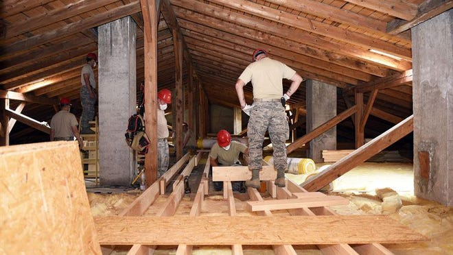 Members of the 219th RED HORSE Squadron verify joists are level on a catwalk in the attic of a barracks at Pocek base, near Postonja, Slovenia. The catwalk was built as a way to easily maneuver through the attic for future maintenance.