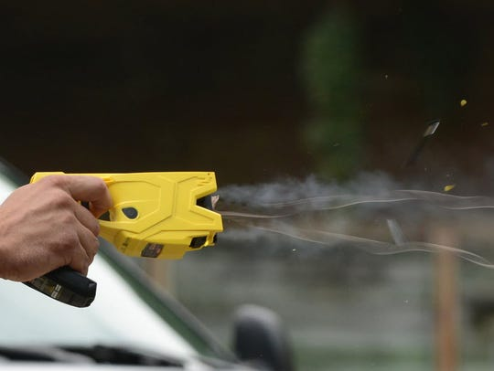 An officer demonstrates the use of a Taser.
