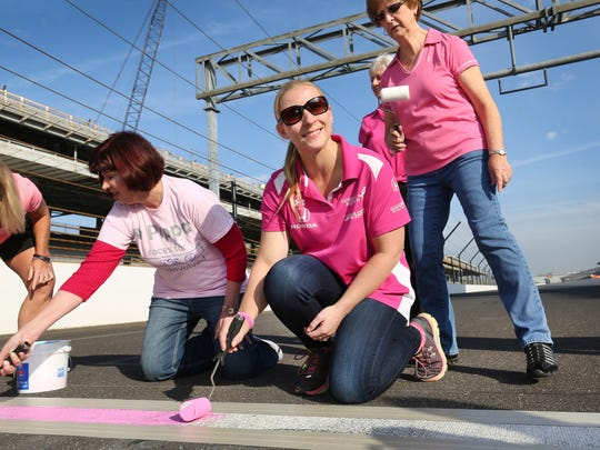 Four-time Indianapolis 500 driver Pippa Mann (foreground) helps breast cancer survivors paint the start/finish line pink at the Indianapolis Motor Speedway in recognition of National Breast Cancer Awareness Month on Thursday, Oct. 8, 2015. Mann, a driver for Dale Coyne Racing, is an ambassador for Susan G. Komen. This is the first time the line has been anything other than white and will remain pink until being repainted at the end of the month.