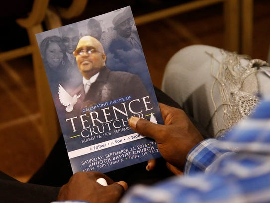 A man is pictured holding a program at Terence Crutcher's