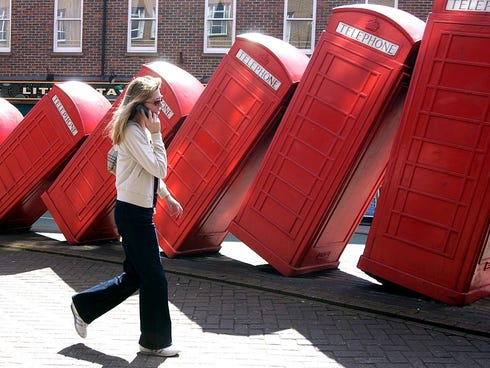 A pedestrian speaking on a mobile phone walks past a series of old red British phone boxes modeled into a work of art in 2004 in Kingston town centre in southwest London.
