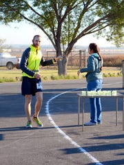 Justin Hill stops for a drink of water at mile 8 at the Pecos River Challenge Sunday in Carlsbad.