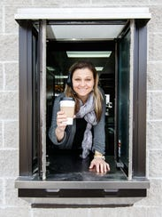 Owner Julie Sokolowski of Cafe Buzzz in Wales serves hot coffee from the drive-thru window on Friday, March 16. The establishment offers coffee drinks, breakfast and lunch sandwiches, salads, soups, blended smoothies and self-serve frozen yogurt with all the toppings.