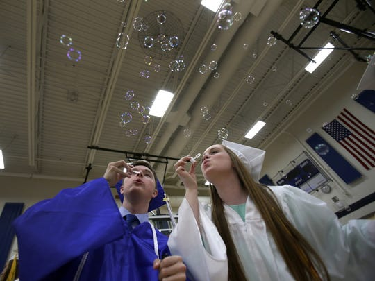 Grant Anderla and Kaitlyn Sawin have fun blowing bubbles together moments before the start of the Xavier High School graduation ceremony last May.