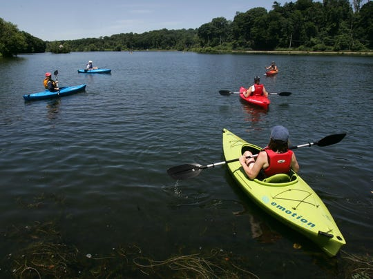 Kayakers on the water at the Tarrytown Lakes, where kayak rentals and lessons are available on summer weekends.