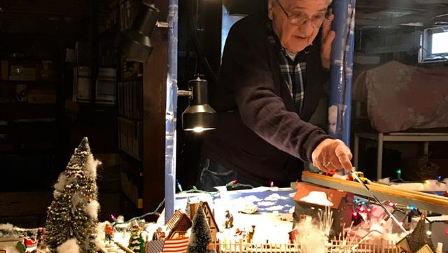 Jerry Eisele of Greece uses a pointer to describe details of his Christmas village, which he spent over 50 years assembling, piece by piece.