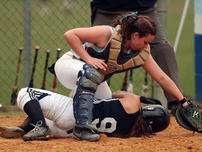 Randolph's Caroline Perlowski slides under the tag of West Morris catcher Rebekah Katz during their MCT softball second-round game, April 22, 2014, Chester, NJ.