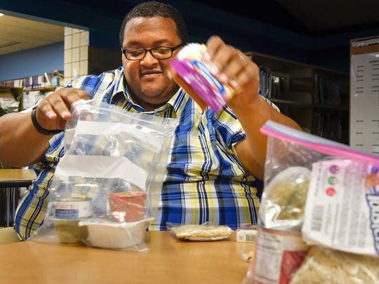 Marcus Paden packs a sample bag of weekend food for a student Friday, Sept. 1 at Discovery School in Waite Park.