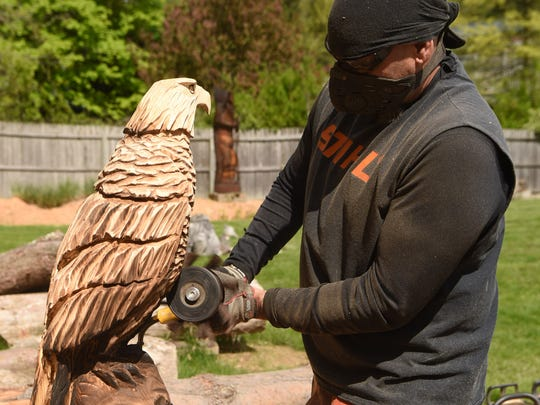 Don Mesuda does some flap sanding on a carving of an eagle at his Hopewell Junction home.