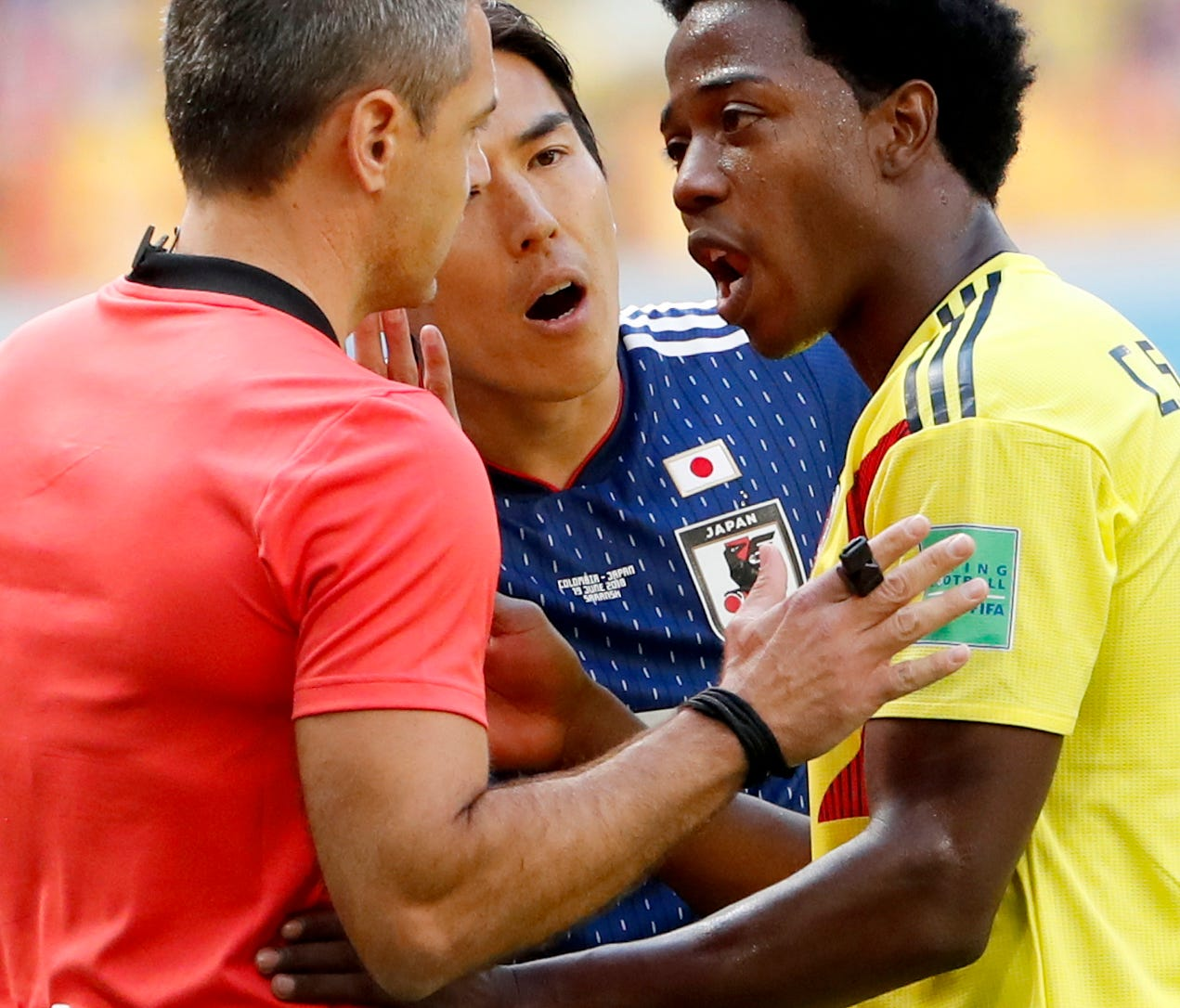 Carlos Sanchez (R) of Colombia reacts after being sent off.