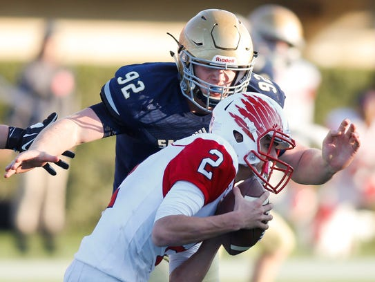 Salesianum's Kyle Cathers prepares to wrap up Smyrna quarterback Nolan Henderson in the 2015 state championship game won by Smyrna 32-26 in overtime at Delaware Stadium. The two are about to become UD teammates.